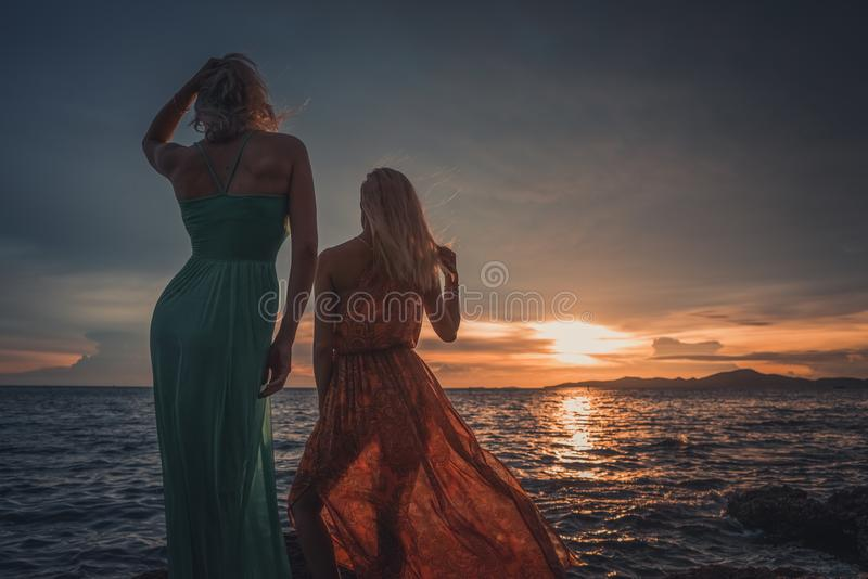 Two fashion models posing in red and turquoise dresses in the rays of the setting sun on a tropical beach. Back to the royalty free stock photo