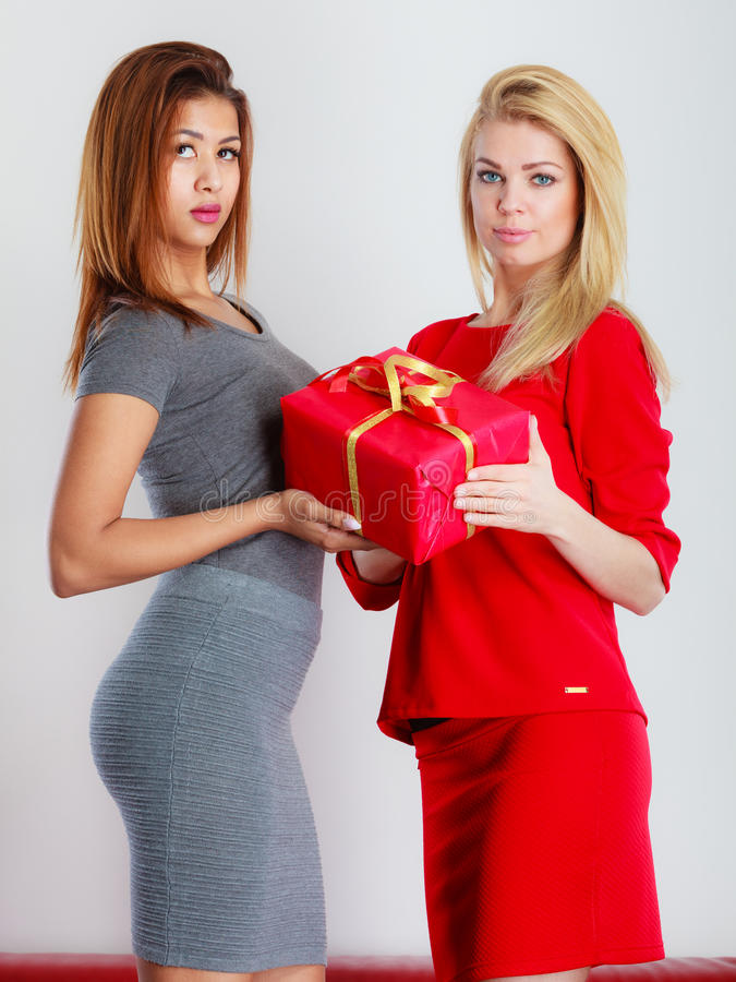 Two fashion women with red box gift. royalty free stock image