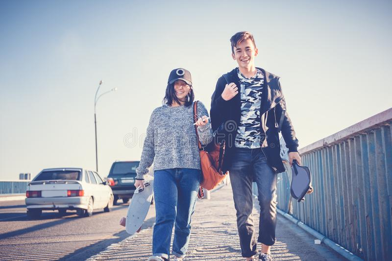 Two Asian teenagers, a boy and a girl of 15-16 years with skateboards in their hands, walk the streets of the city, happiness, yo royalty free stock photo