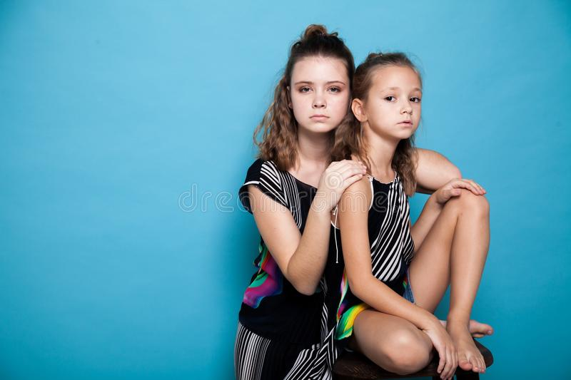 Two fashionable girls posing with a camera on a blue background stock image