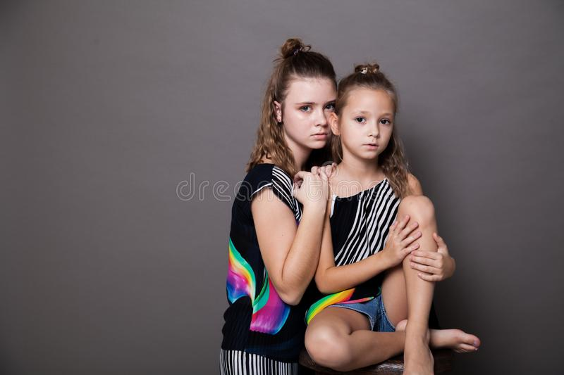 Two fashionable girls sisters in beautiful clothes portrait royalty free stock photography