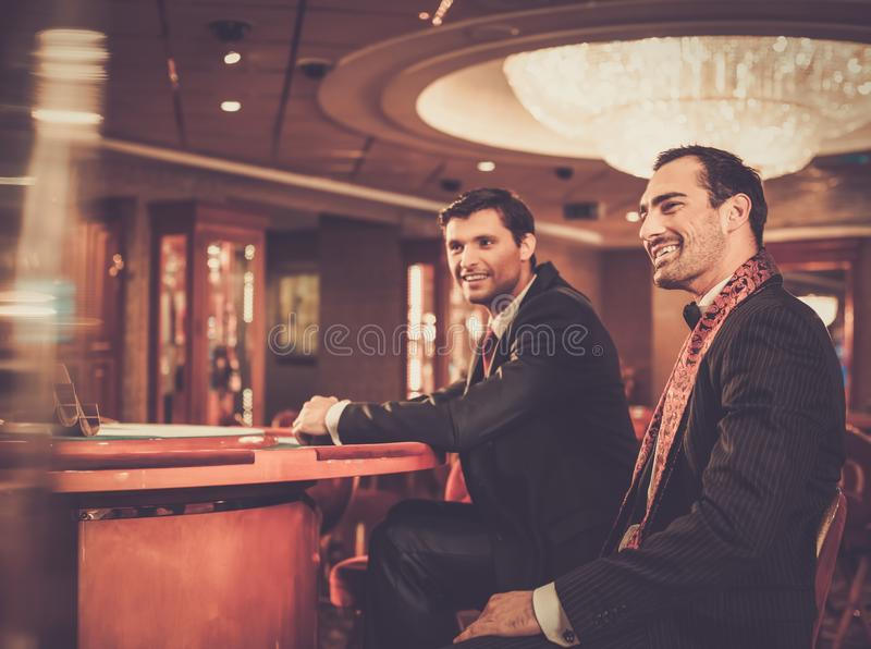 Two fashionable men behind table in a casino. Two fashionable men in suits behind table in a casino stock photos