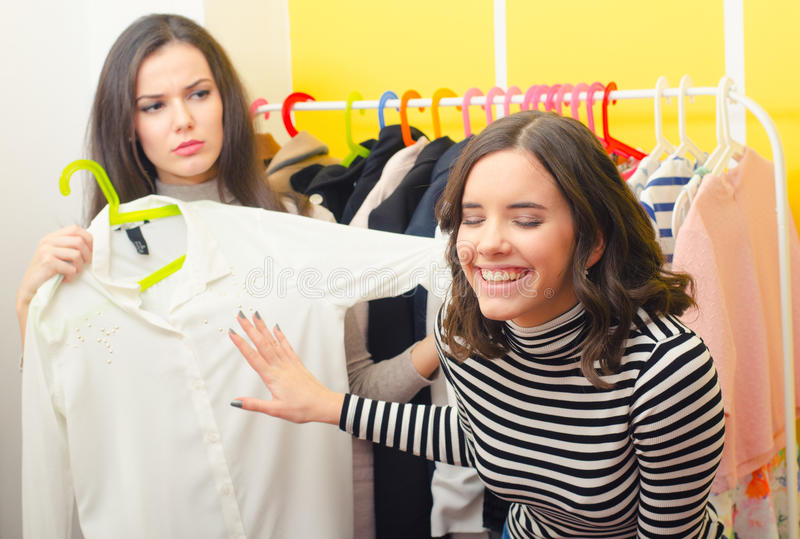 Two fashionable teenage girlfriends choosing clothes. At home royalty free stock photo