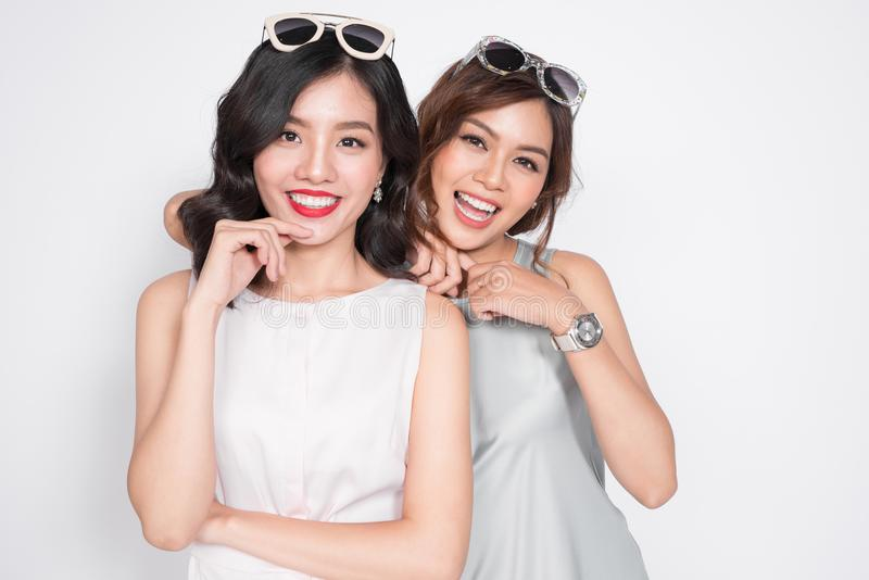 Two fashionable women in nice dresses standing together and having fun stock photo