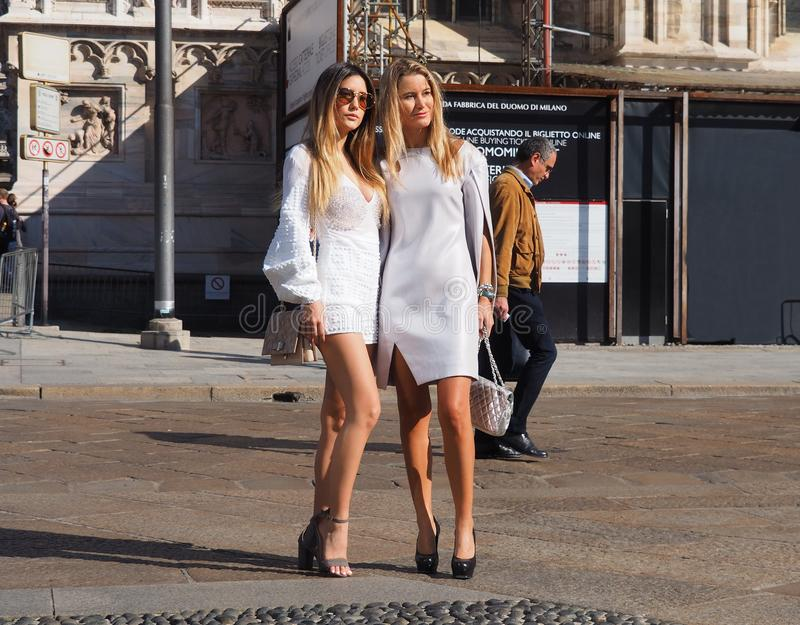 MILAN - SEPTEMBER 21: Two fashionabl women posing for photographers before GENNY fashion show, during Milan Fashion Week. Two fashionable women in white posing stock photos