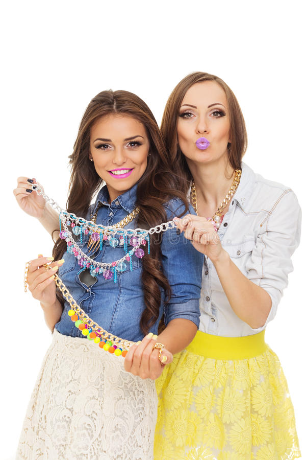 Two fashionable young Hispanic and Caucasian women choosing a necklace. Two fashionable young Hispanic and Caucasian women with long brown hair wearing modern stock images