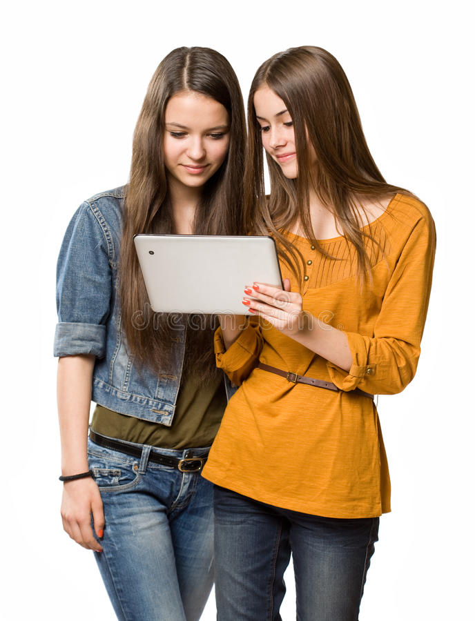 Teenagers having fun with a tablet computer. Two fashionable young teenagers having fun with a tablet computer stock photo