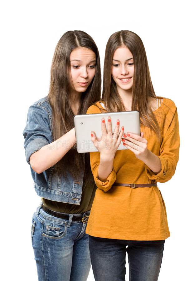 Teenagers having fun with a tablet computer. Two fashionable young teenagers having fun with a tablet computer royalty free stock photos