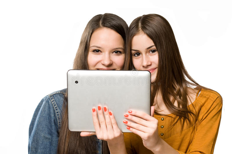 Teenagers having fun with a tablet computer. Two fashionable young teenagers having fun with a tablet computer royalty free stock images
