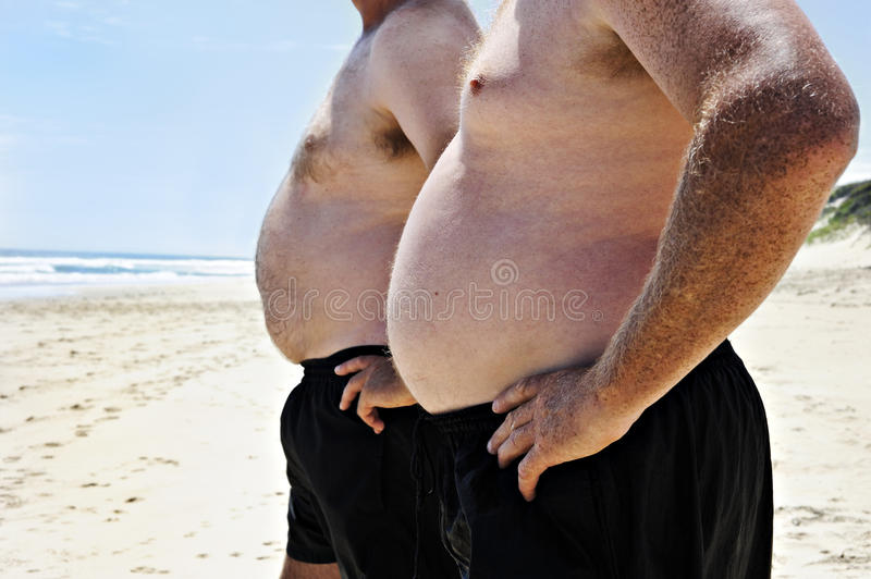 Two fat men on a beach stock images