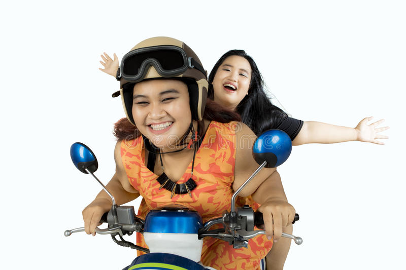 Two fat women driving motorcycle together stock photo