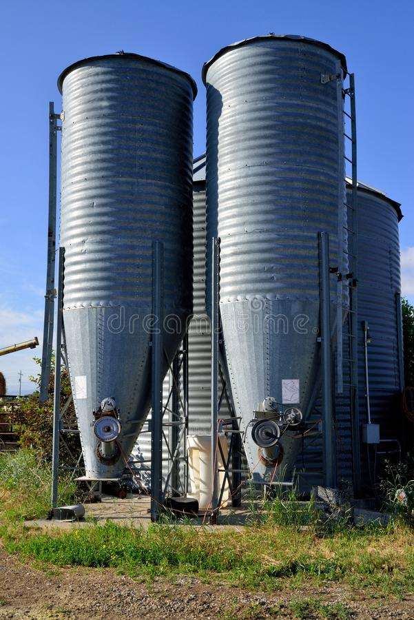 Two feed silos on a small ranch. These metal feed silos hold the fodder for the cows, pigs and chickens on a small Montana ranch stock photography
