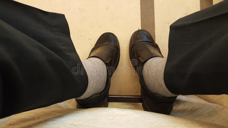 Two feet with formal black shoes. Concept of busy executive, business man sitting on meeting chair with black shoes and trousers seen from above royalty free stock images