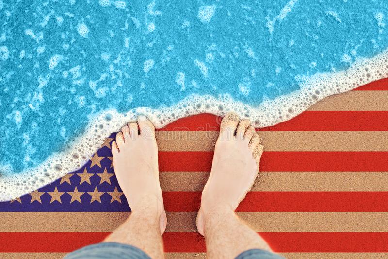 Two feet on the sunny sandy beach with flag USA. Top View on surf.  royalty free stock photos