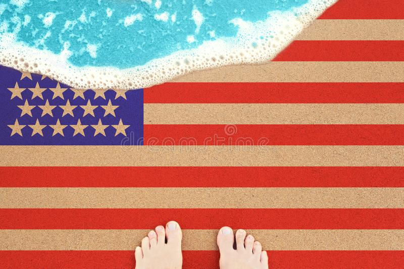 Two feet on the sunny sandy beach with flag USA. View from top on surf.  royalty free stock photo