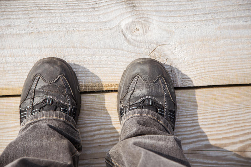 Two feet on a wooden footpath during the hiking. In an early spring royalty free stock photos