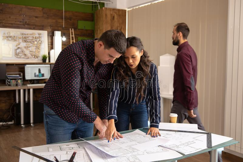 Two fellow architects standing at the table and discussing the project stock image