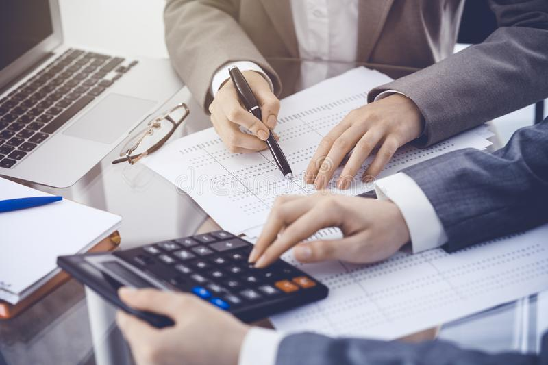 Two female accountants counting on calculator income for tax form completion hands close-up. Business and audit concept.  royalty free stock photos