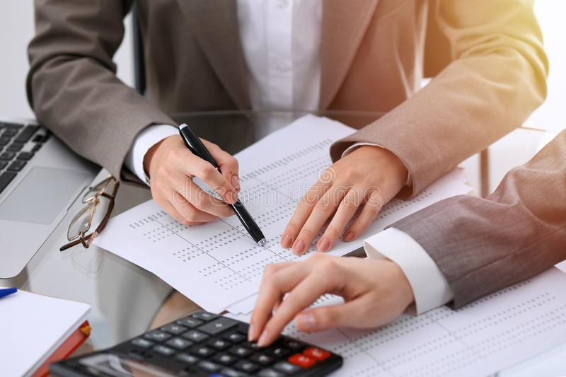 Two female accountants counting on calculator income for tax form completion hands close-up. Business and audit concept.  royalty free stock image