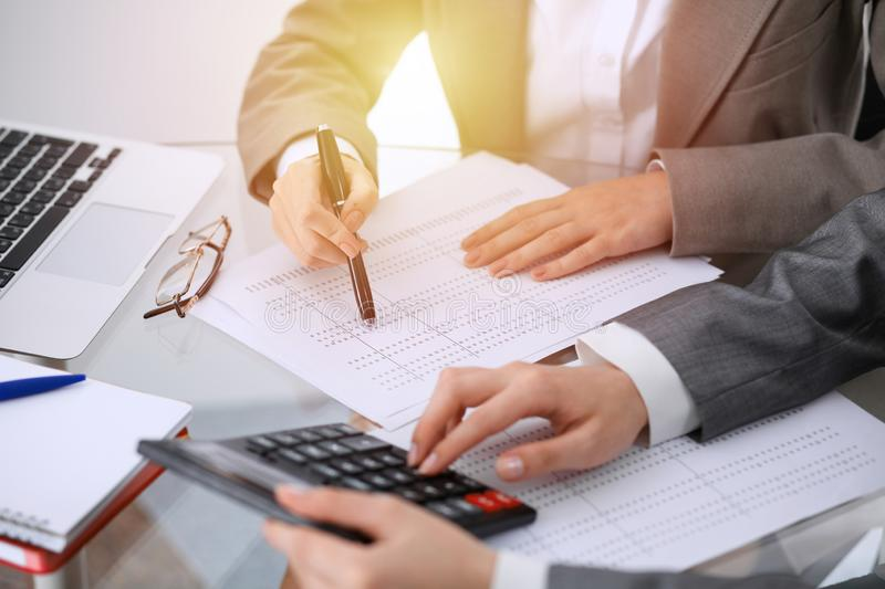 Two female accountants counting on calculator income for tax form completion hands close-up. Business and audit concept.  stock photo