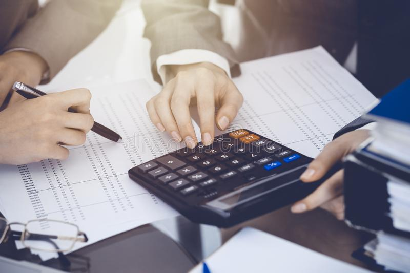 Two female accountants counting on calculator income for tax form completion hands close-up. Business and audit concept.  royalty free stock photography