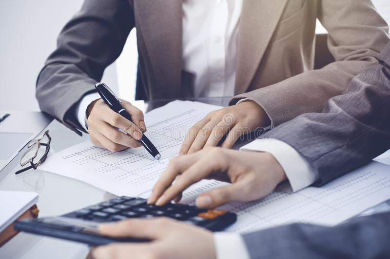 Two female accountants counting on calculator income for tax form completion hands close-up. Business and audit concept.  stock photos