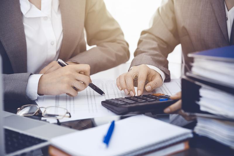 Two female accountants counting on calculator income for tax form completion hands close-up. Business and audit concept.  stock images