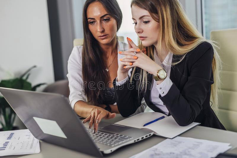 Two female accountants working together on financial report using laptop sitting at desk in account department royalty free stock photo