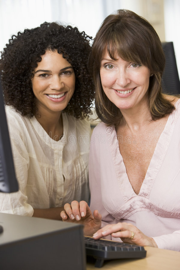 Two female adult students working on a computer. Together royalty free stock photos