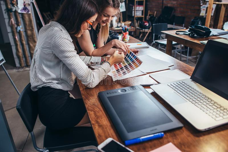 Two female architects working together using color swatches sitting at desk with laptop, graphic tablet in design studio royalty free stock photography