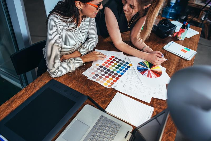 Two female architects working together using color swatches sitting at desk with laptop, graphic tablet in design studio.  stock image