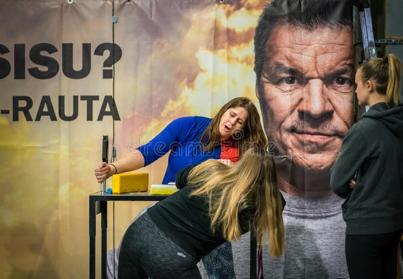 Two female arm wrestlers against a large ad. STOCKHOLM, SWEDEN - JANUARY 13, 2018: Two female arm wrestlers and one spectator training in front of a large ad stock images