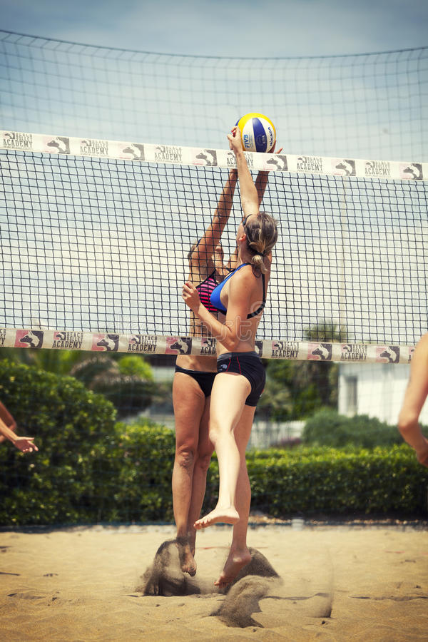 Two female beach volleyball players compete for the ball. Net stock photo