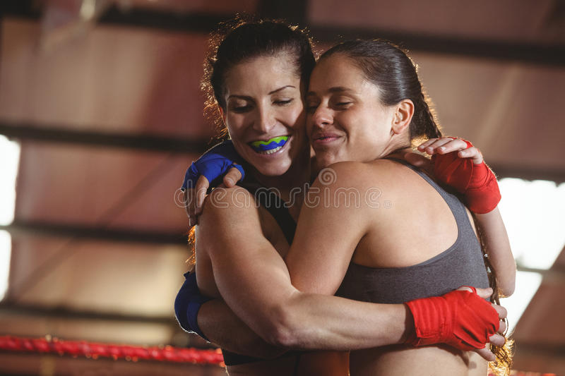 Two female boxers hugging each other in the ring stock photos