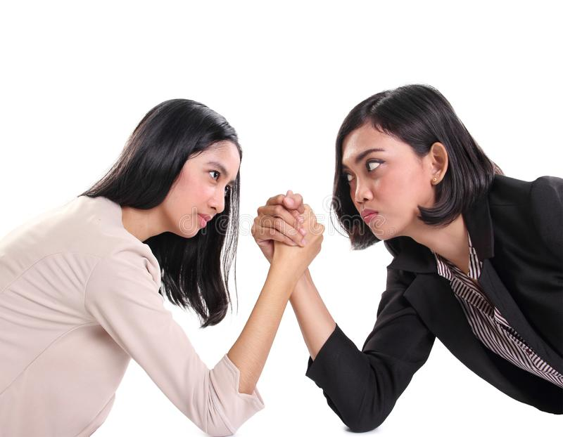 Two female business workers face each other in arm wrestling battle, white background. Two female business workers stare against each other with serious faces stock photos