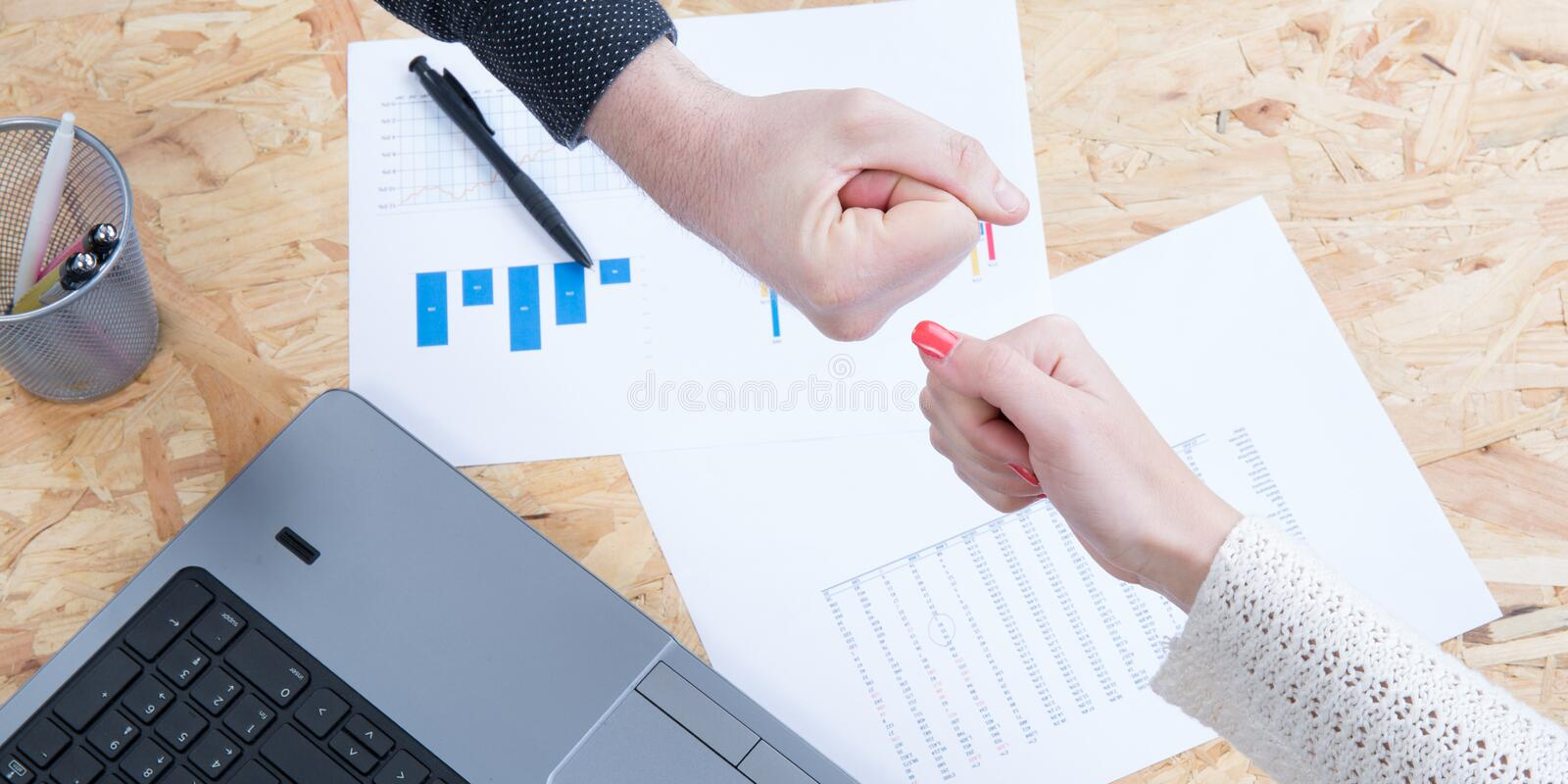 Two female colleagues are beating their fists to celebrate their good economic results top view stock images