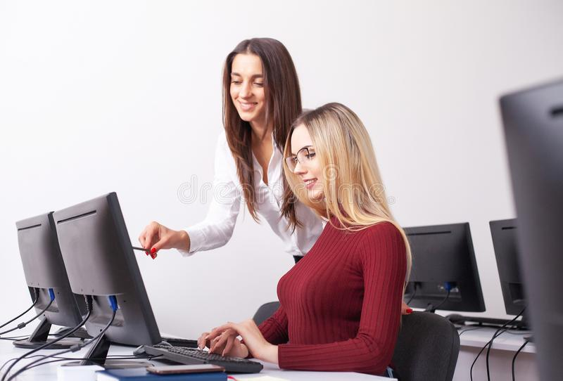 Two female colleagues in office working together. stock photos