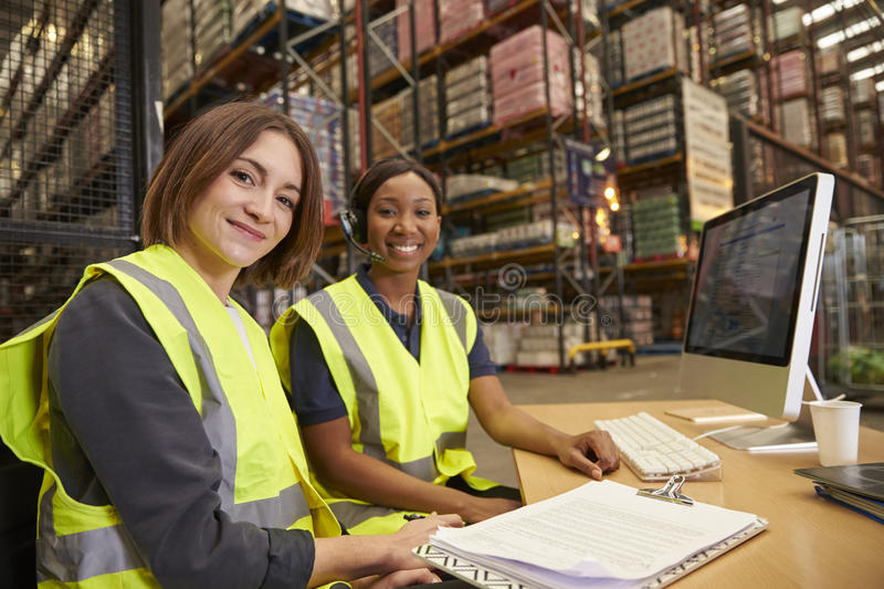 Two female colleagues in a warehouse office look to camera stock photos