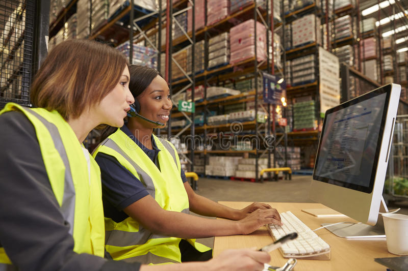Two female colleagues working in the office of a warehouse royalty free stock photo
