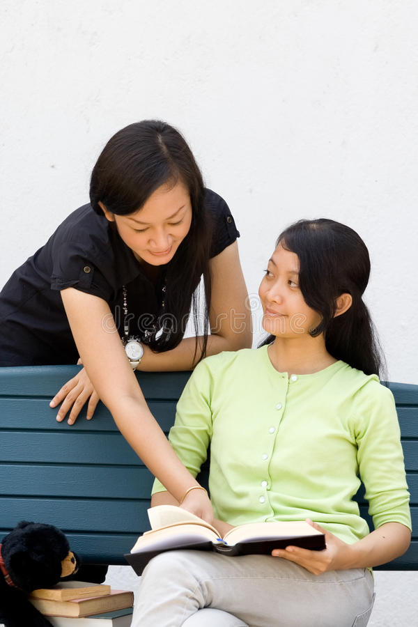 Two Female College Student Discussing A Literature Royalty Free Stock Photography