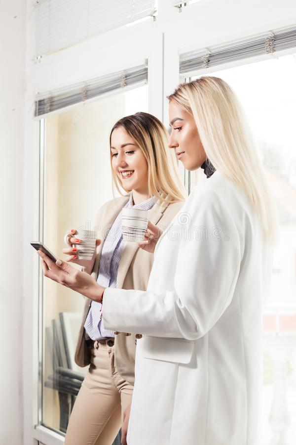 Two female collegues discussing and using phone stock images