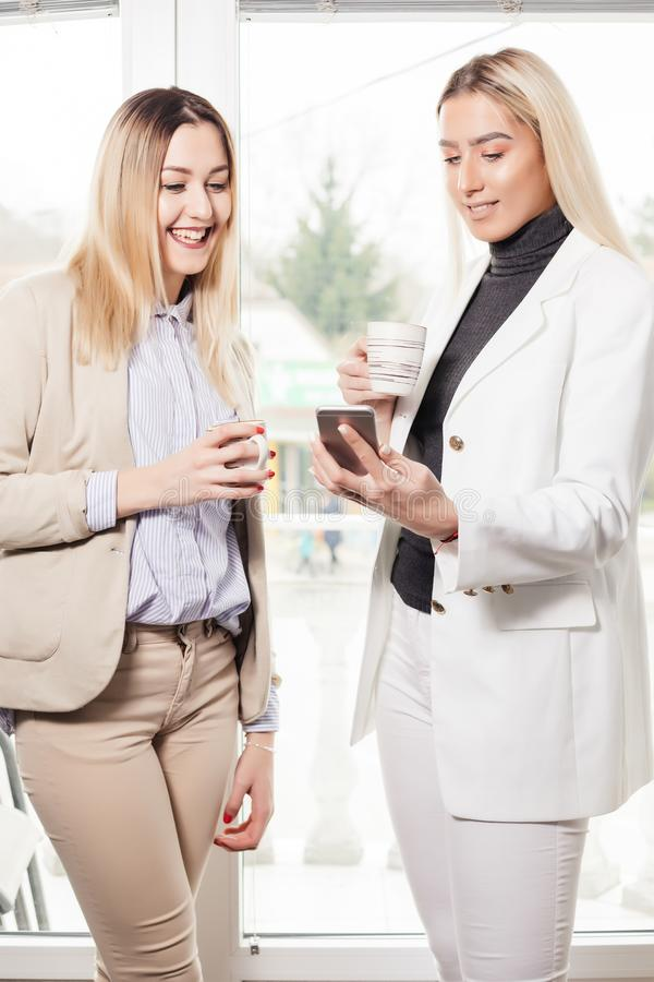 Two female collegues looking at mobile phone stock photos
