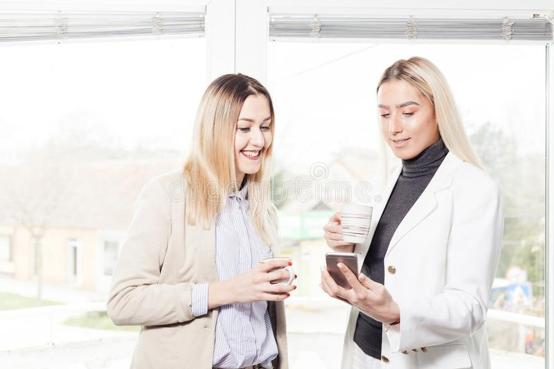 Two female collegues looking at mobile phone royalty free stock photos