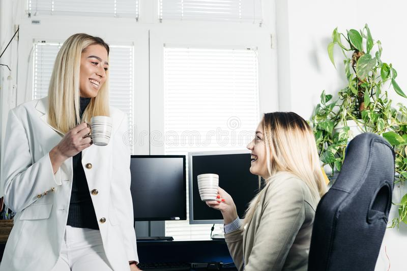 Female collegues drinking coffee and discussing stock photo