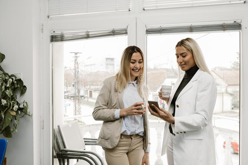 Two female collegues looking at mobile phone royalty free stock photo