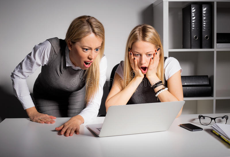 Two female coworkers looking at computer in disbelief royalty free stock image