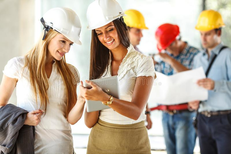 Two female engineers visit the construction site. stock image
