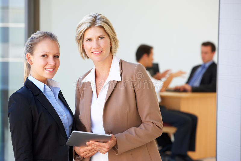 Two Female Executives Using Tablet Computer With Office Meeting In Background stock photo