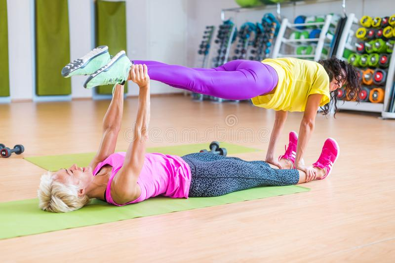 Two female fitness models doing yoga exercises, one lying on floor mat holding legs of another above her in a sports royalty free stock photo
