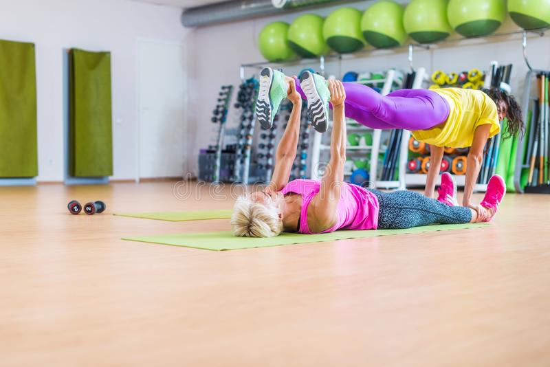 Two female fitness models doing yoga exercises, one lying on floor mat holding legs of another above her in a sports. Two female fitness models doing yoga stock photos
